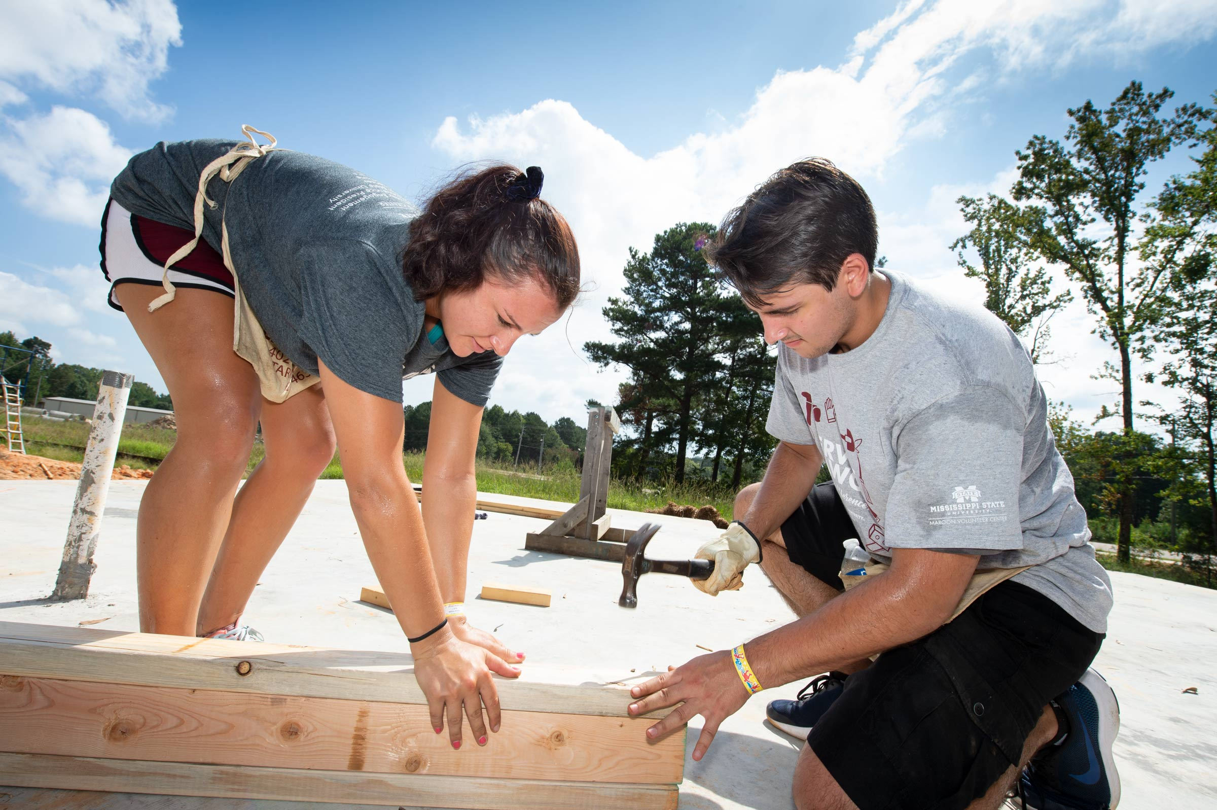 Student Service Dawgs Day Volunteers Amanda Wilson and Garrett Reeves hammer together wall framing at the Habitat for Humanity House.