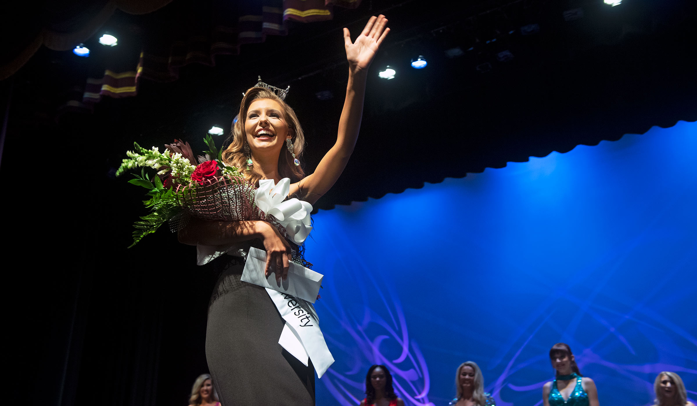 Female student in black evening gown with white sash, roses and crown waving at crowd from stage