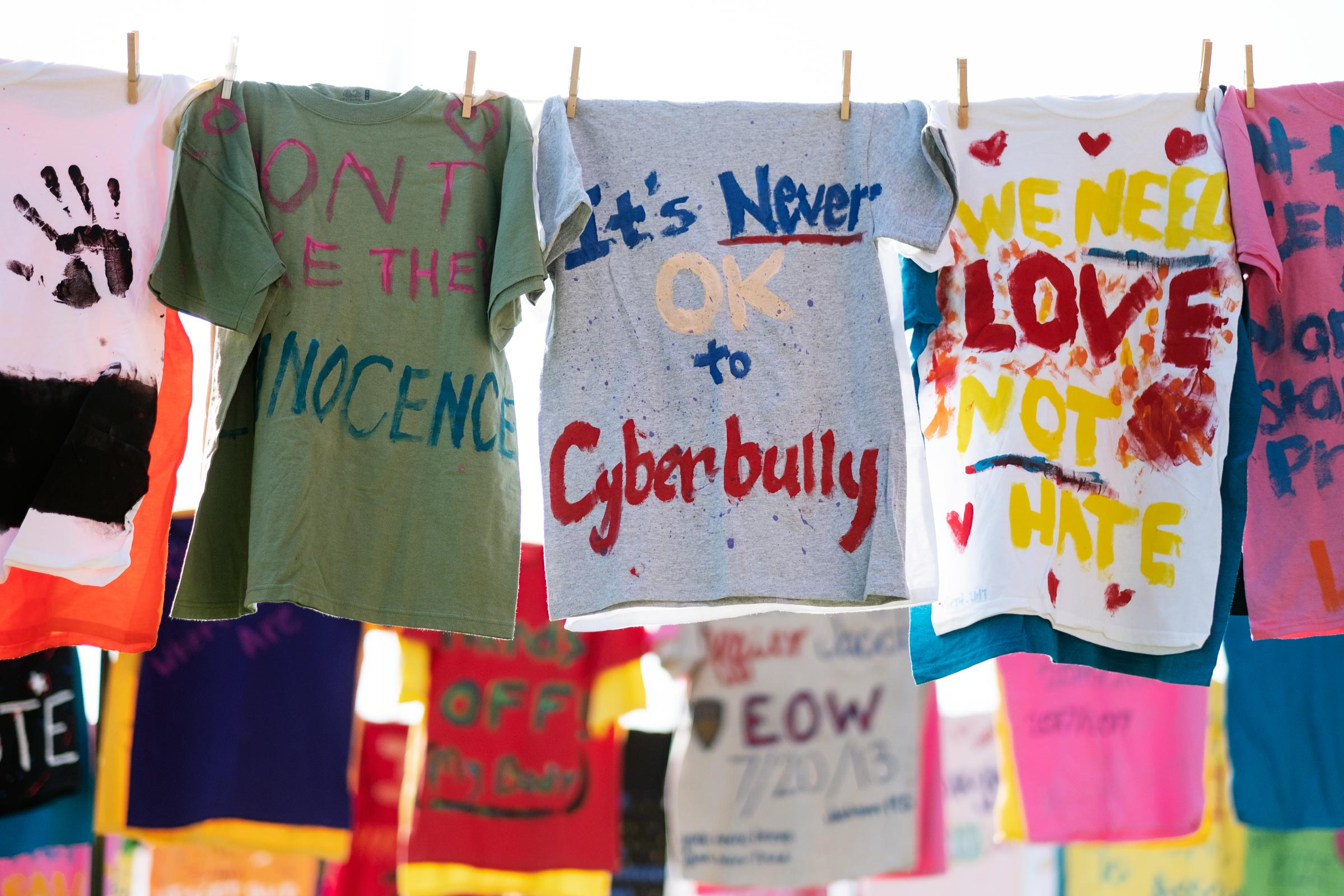 A colorful array of painted t-shirts hang by clothespins as part of the Clothesline Project.