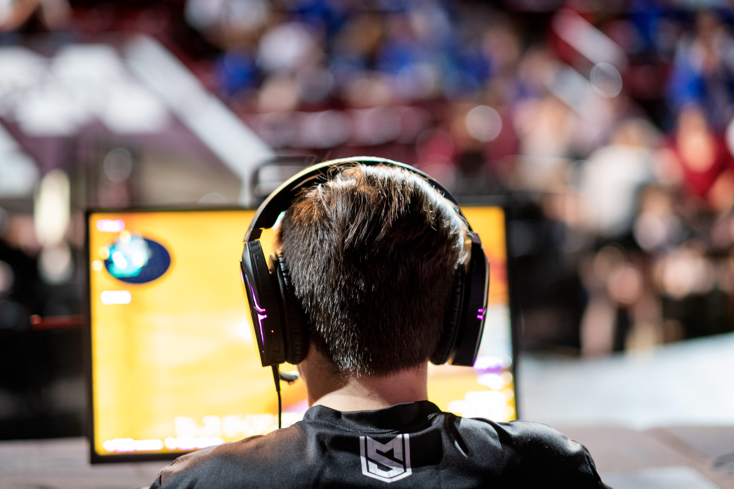 Wearing headphones and framed by the glow of a yellow computer screen, an MSU student eSports team member competes at the Hump.