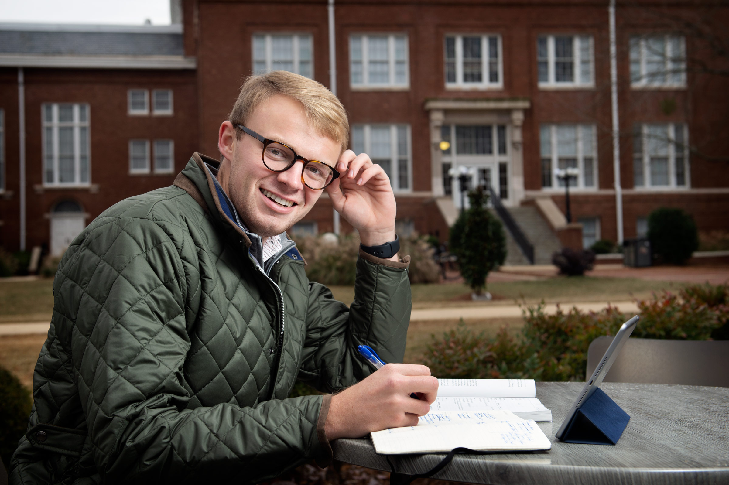 Reid Stevens, pictured at a table in front of Colvard Student Union with Lee Hall in the background