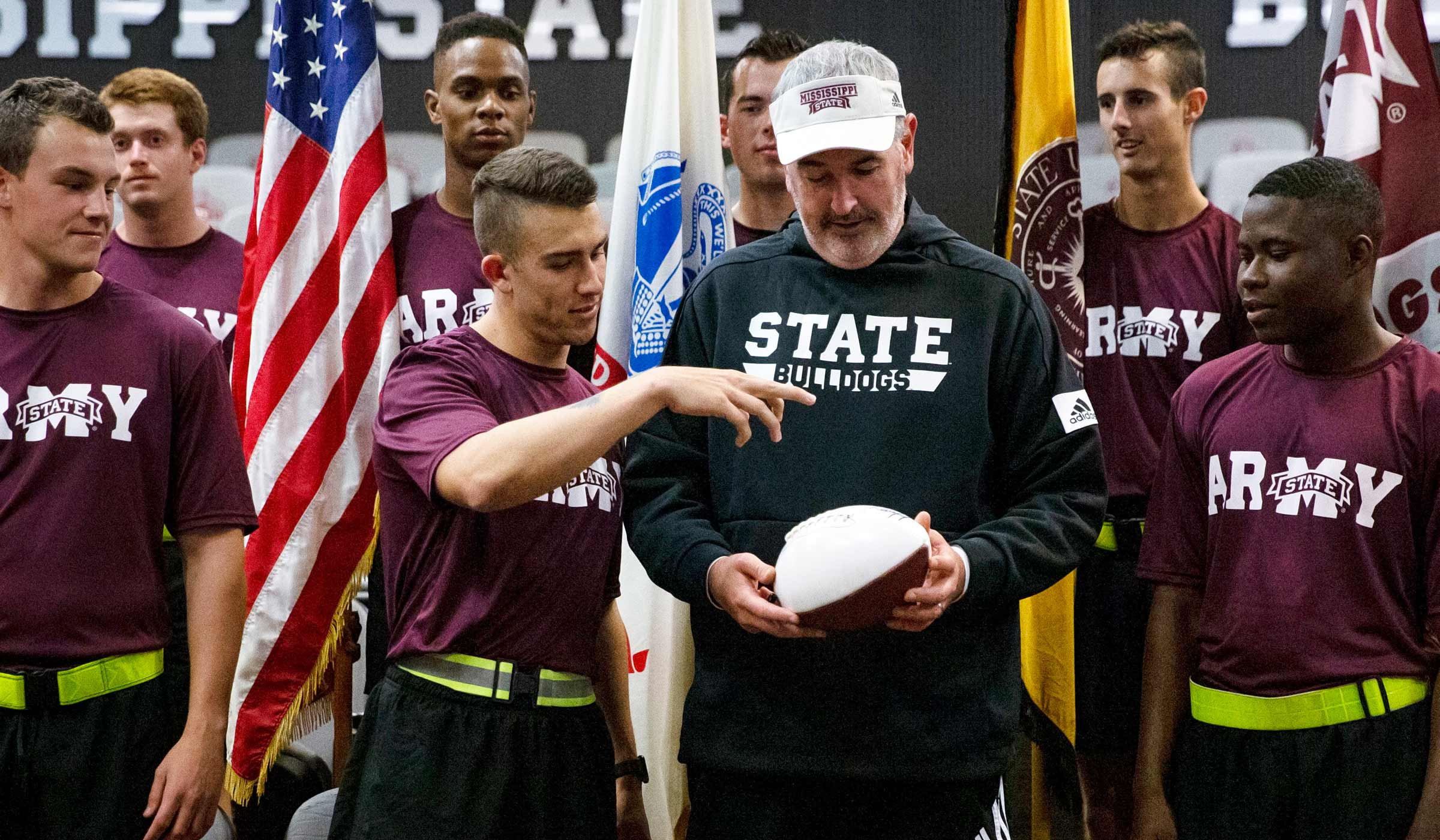 Man in black sweats holding football with Army ROTC in maroon shirts and flags.