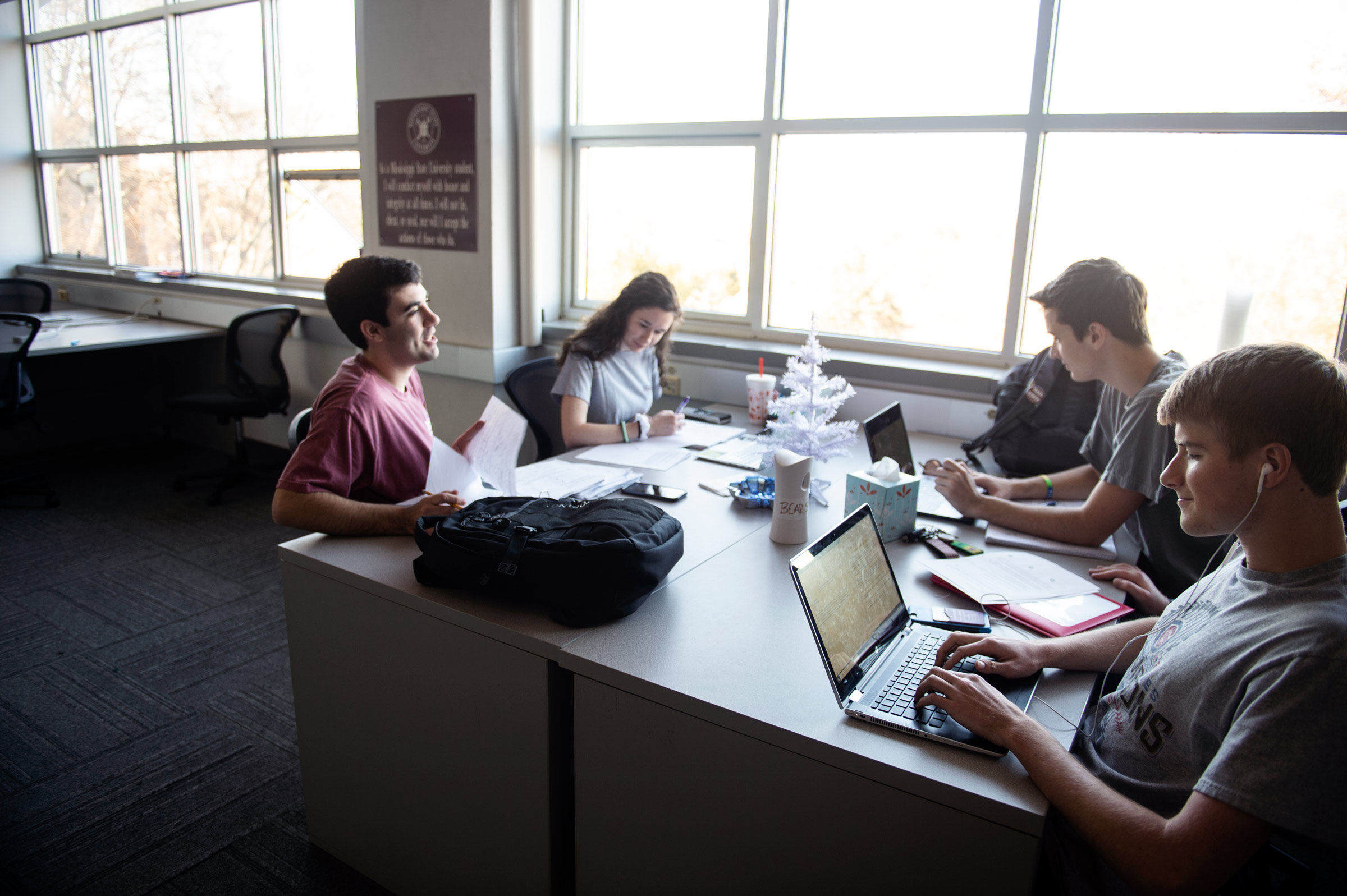 Four geosciences students study for December finals in a Hilbun study lab with a small Christmas tree in the table's center.
