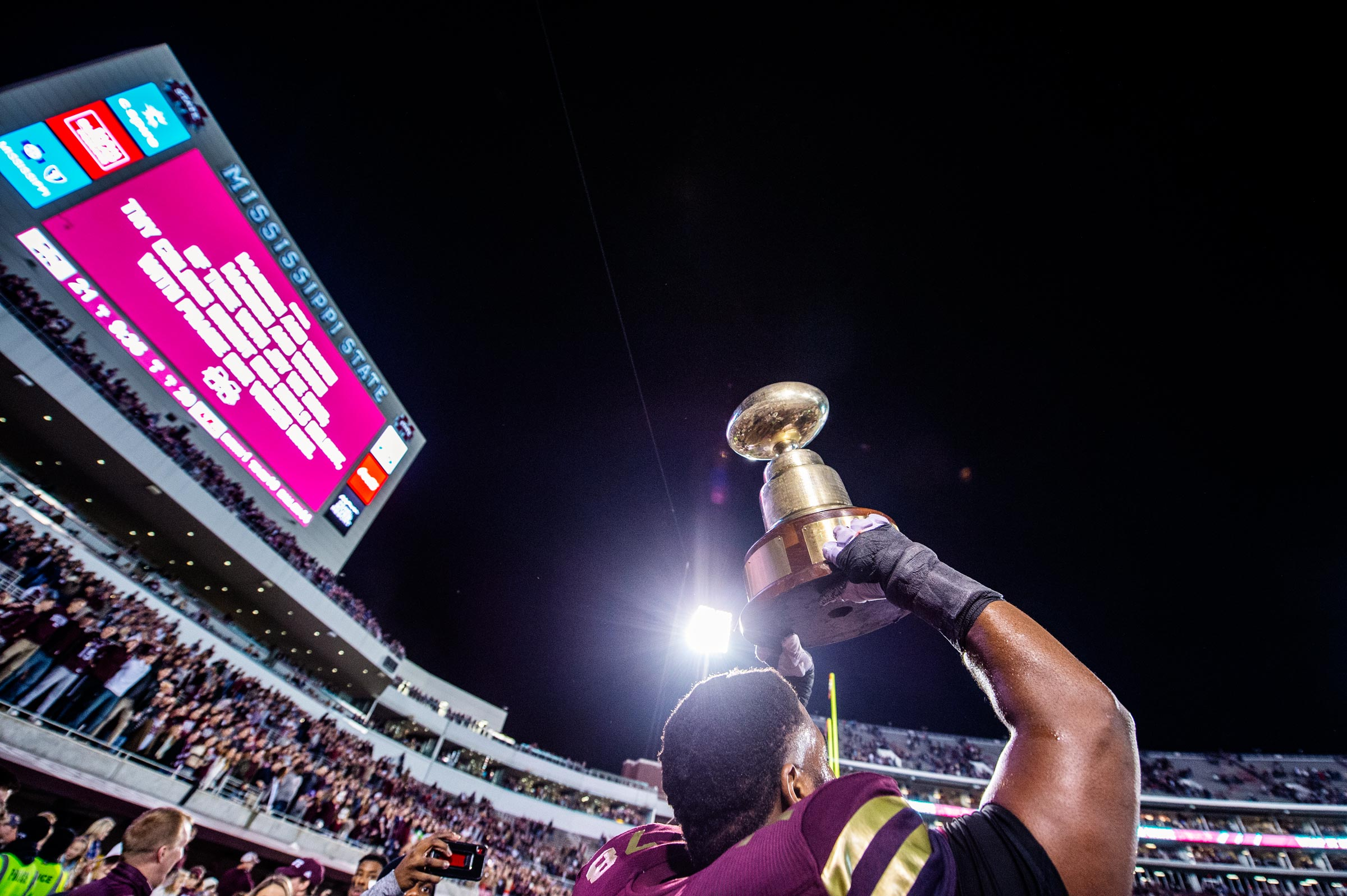 With the nighttime Davis Wade Stadium wrapping around him, an MSU player holds the Egg Bowl trophy high over his head in celebration