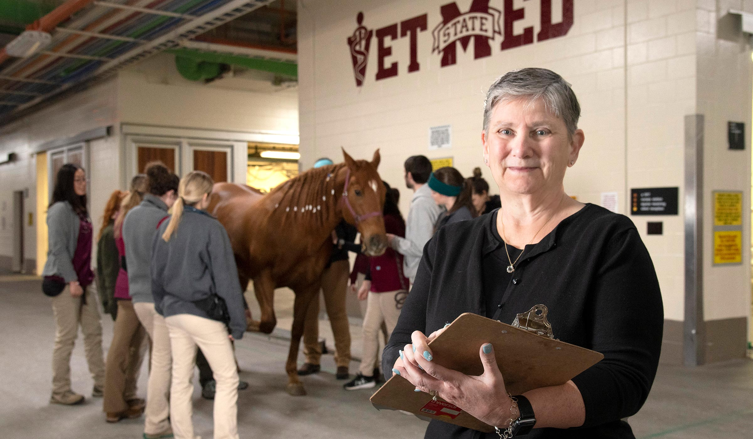 Pauline Prince, pictured in front of a horse and veterinary students.