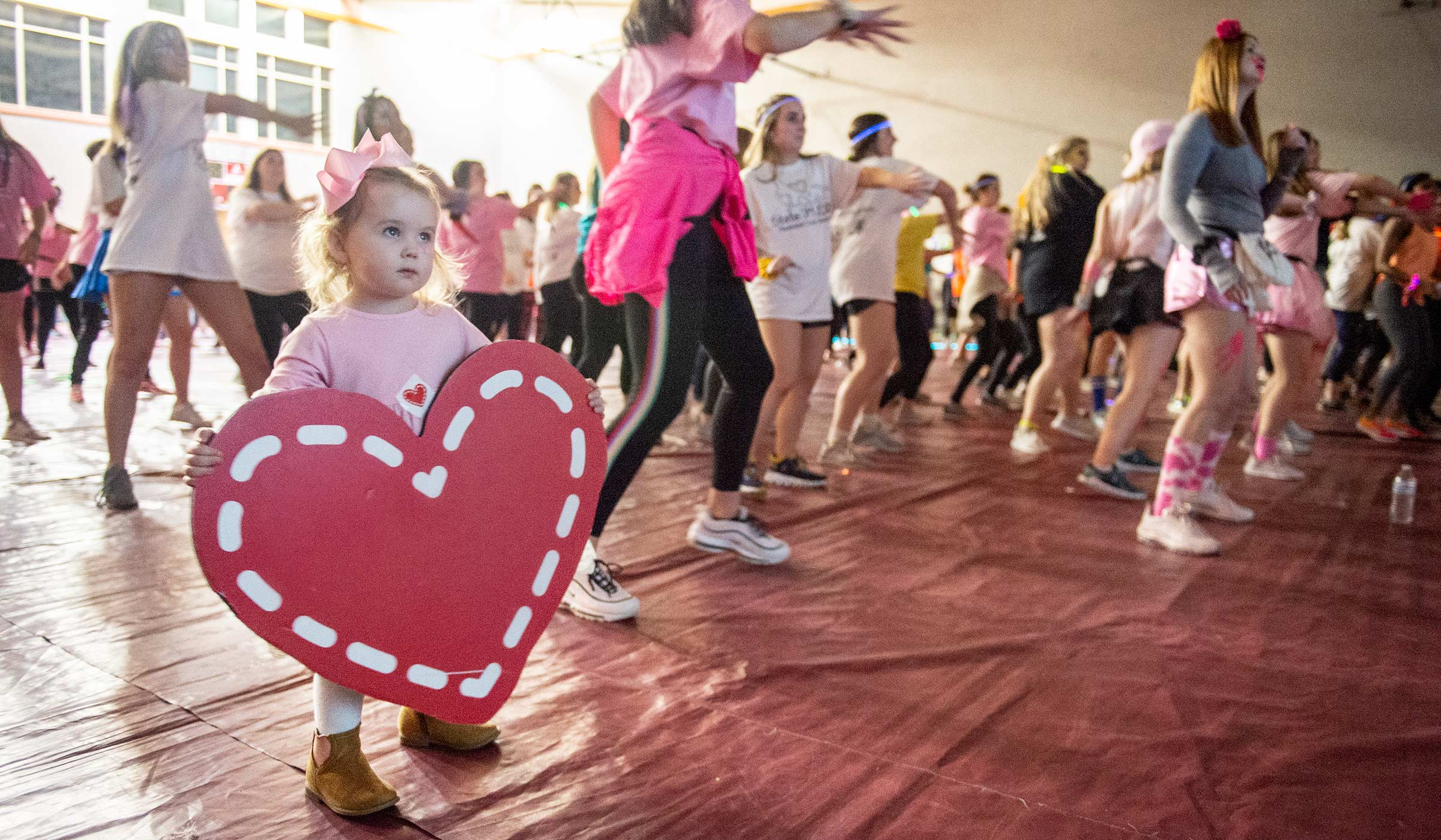 Two year old Mary Michael Kimbrough holds a Dance Marathon heart on the dance floor, while MSU students dance around her.