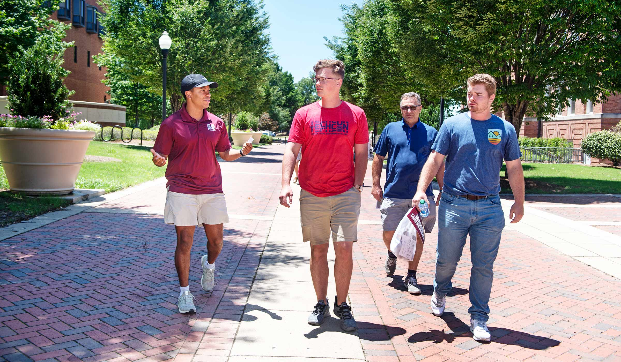 Student in baseball cap and maroon polo talking to three men on brick walkway