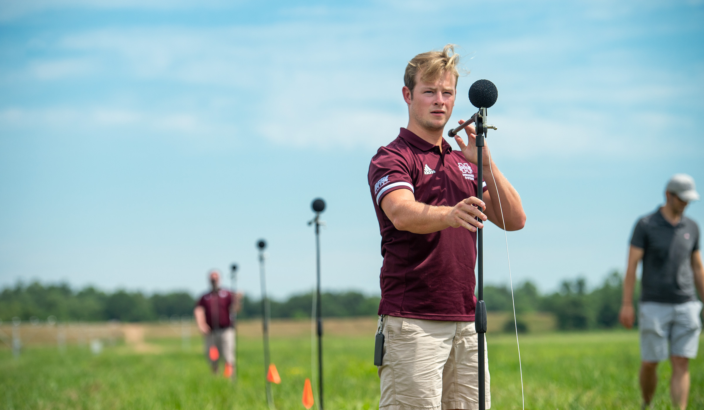 In the foreground of an array of microphones stretched out in a field ajacent to Greenwood-LeFlore Airport, a Raspet engineer in the foreground adjusts the microphone angle.