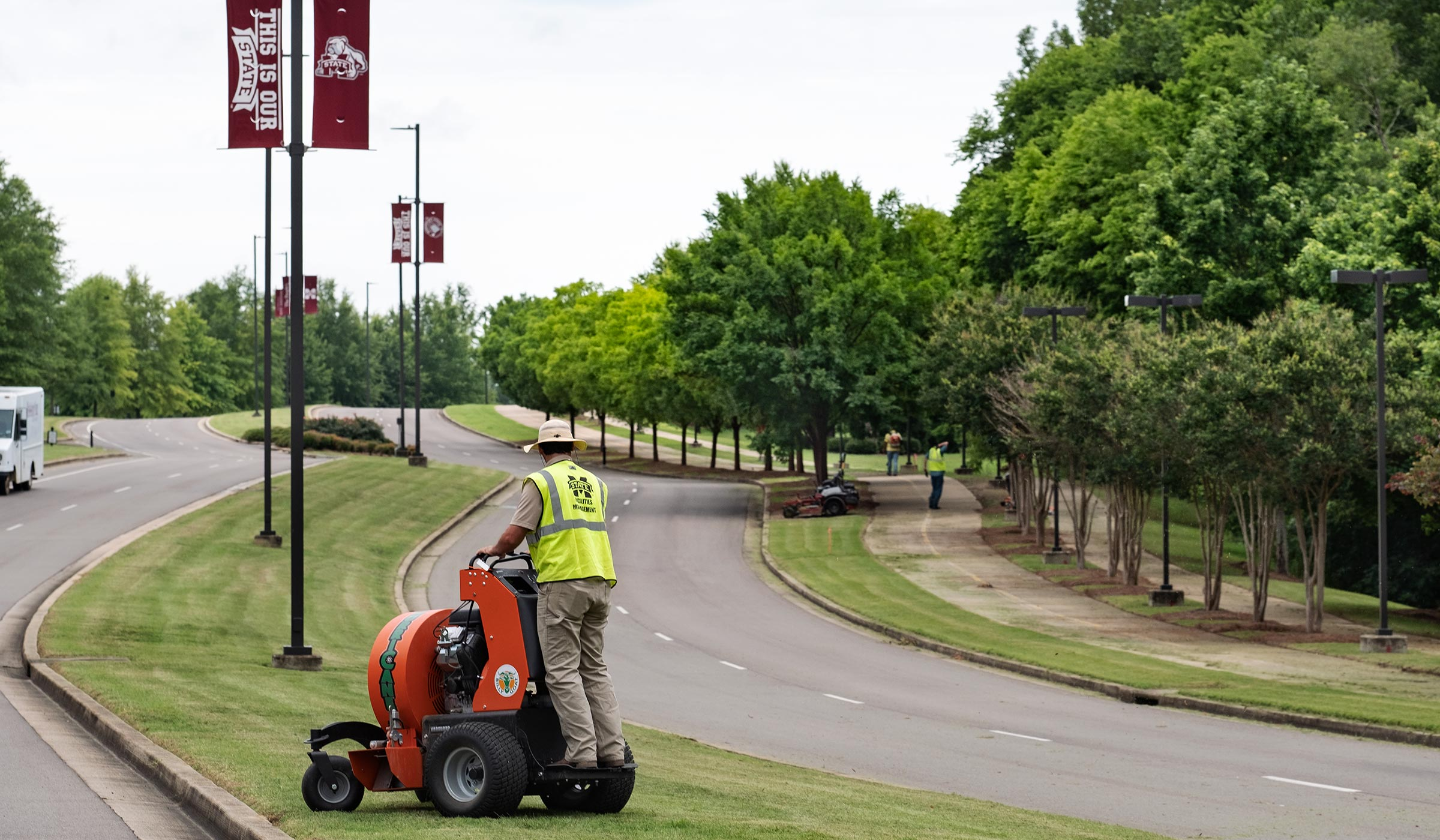 With a worker tending to the grass in the cneter median, MSU's landscape crew works to maintain MSU's North Entrance Drive..