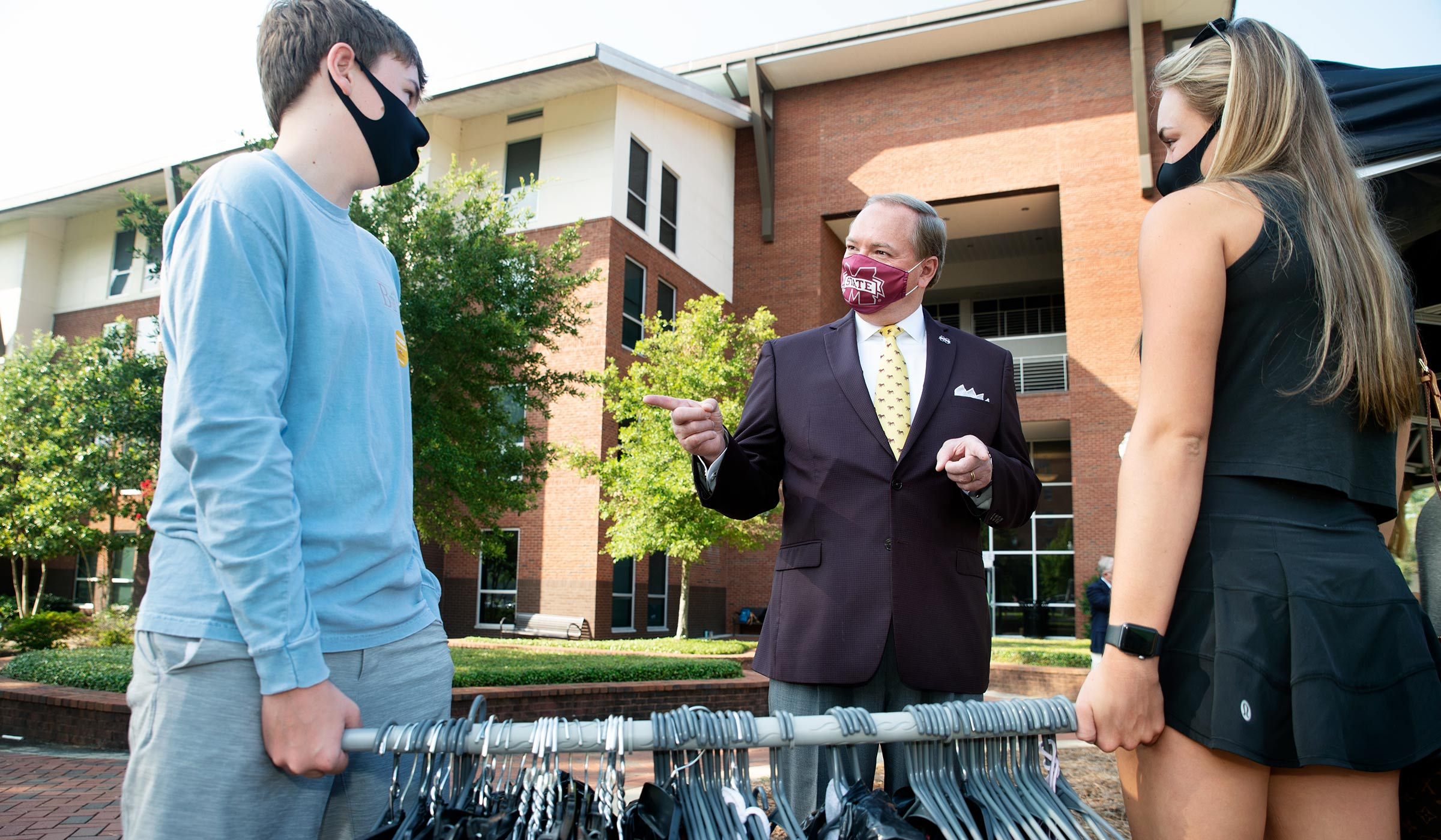 With Oak Hall behind them on Move-in Day, President Keenum speaks to a pair holding a rod filled with hanging clothes.