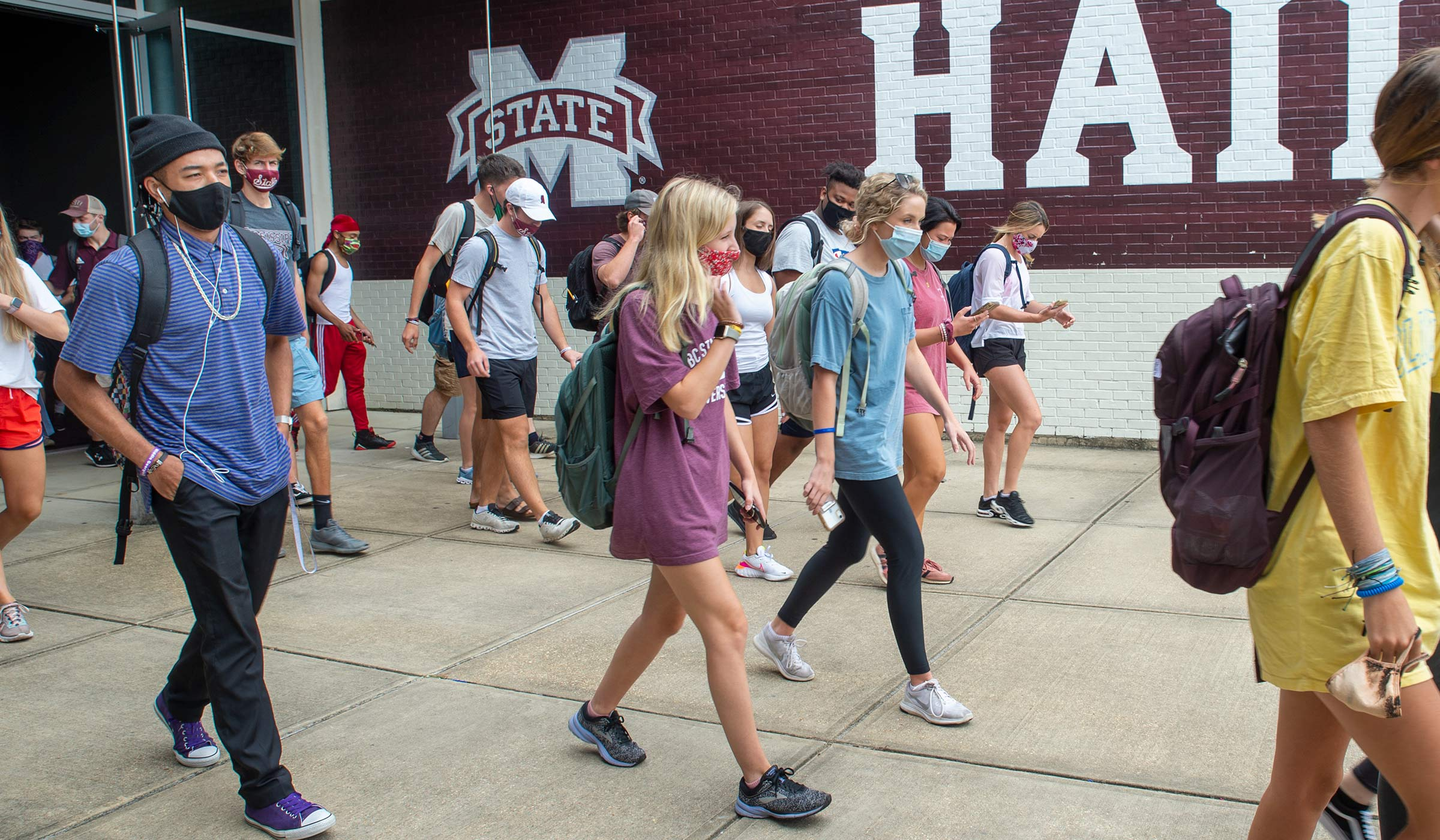 With a bit of the Hump's Hail State sign behind them, masked students exit the doors of the Mize Pavillion entrance after class.