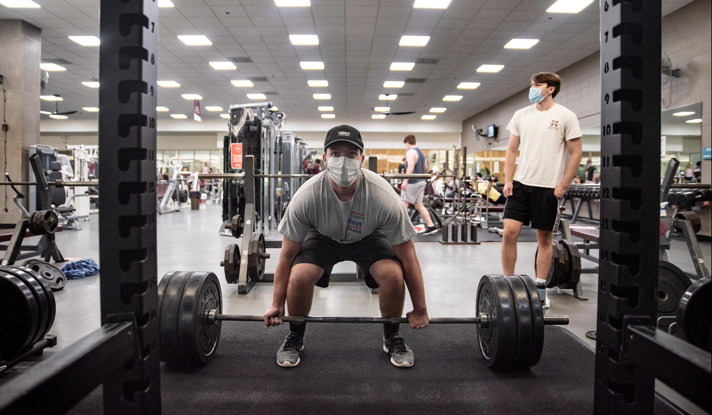 Masked student lifts heavy weights in Sanderson weight room.