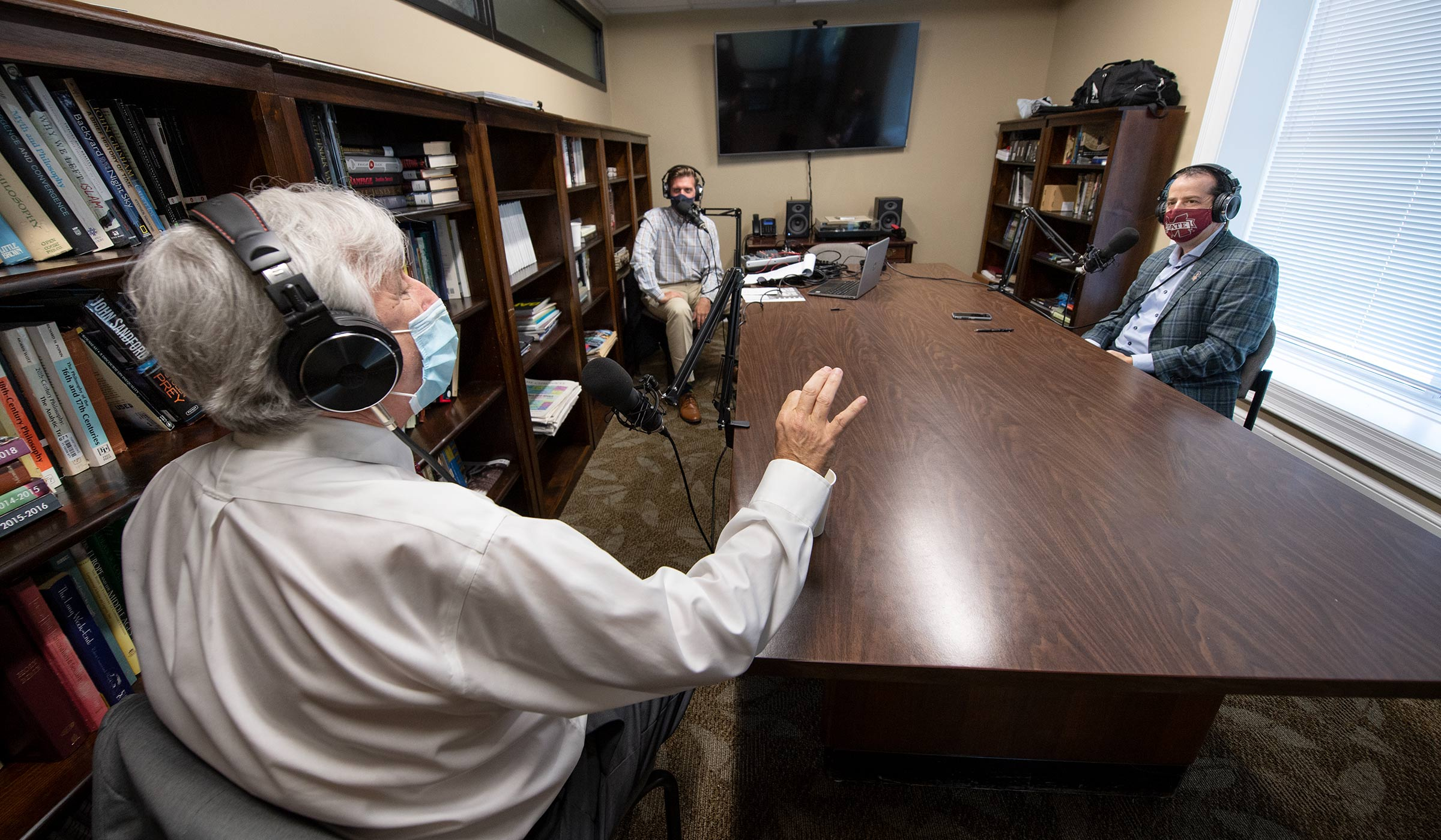 With all three wearing headphones and face masks, Astronaut Scholar Program representative Ray Gildea speaks with across a table with honors Professor David Hoffman and Wade Leonard for an Honors podcast.