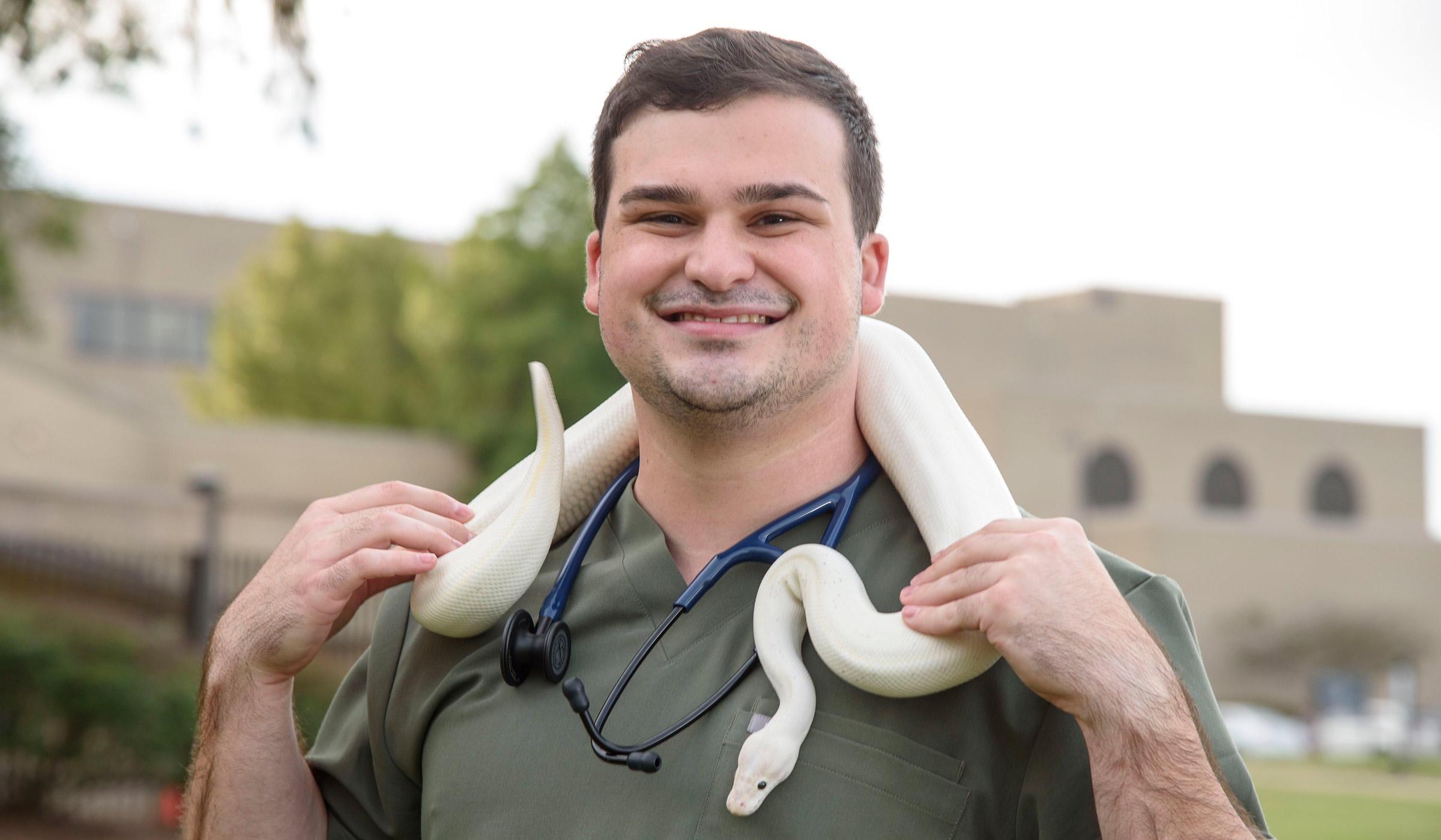 Travis Noto, pictured with a pet snake draped over his shoulders.