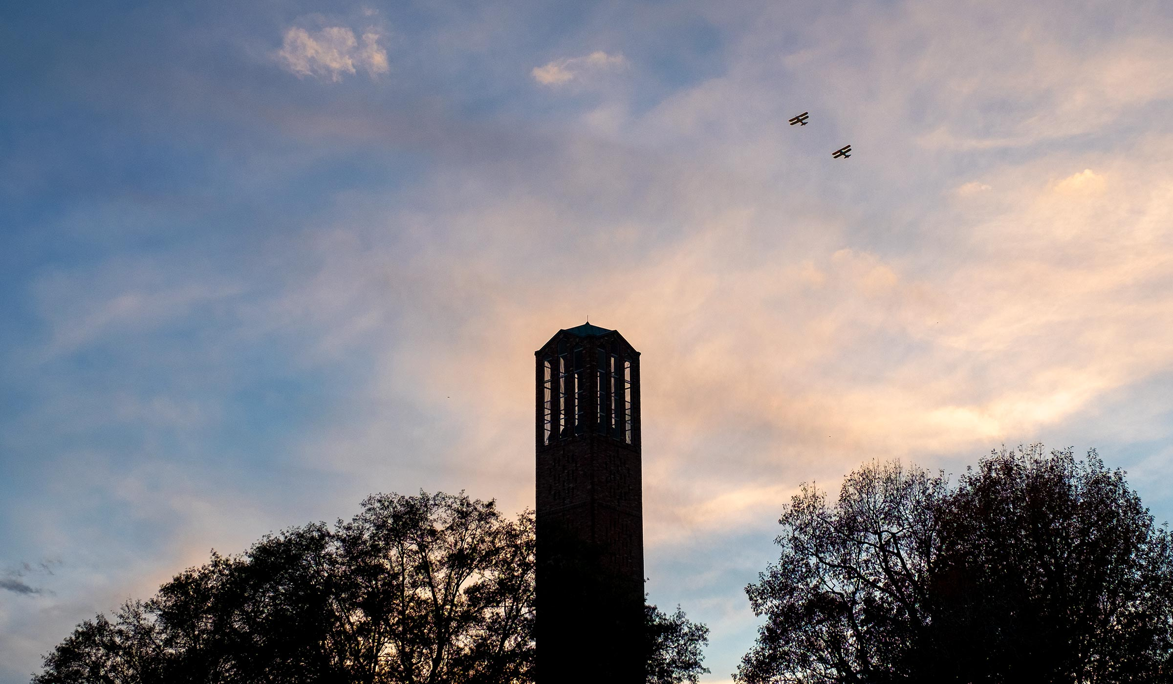 Chapel tower with pair of biplanes against the sunset clouds.