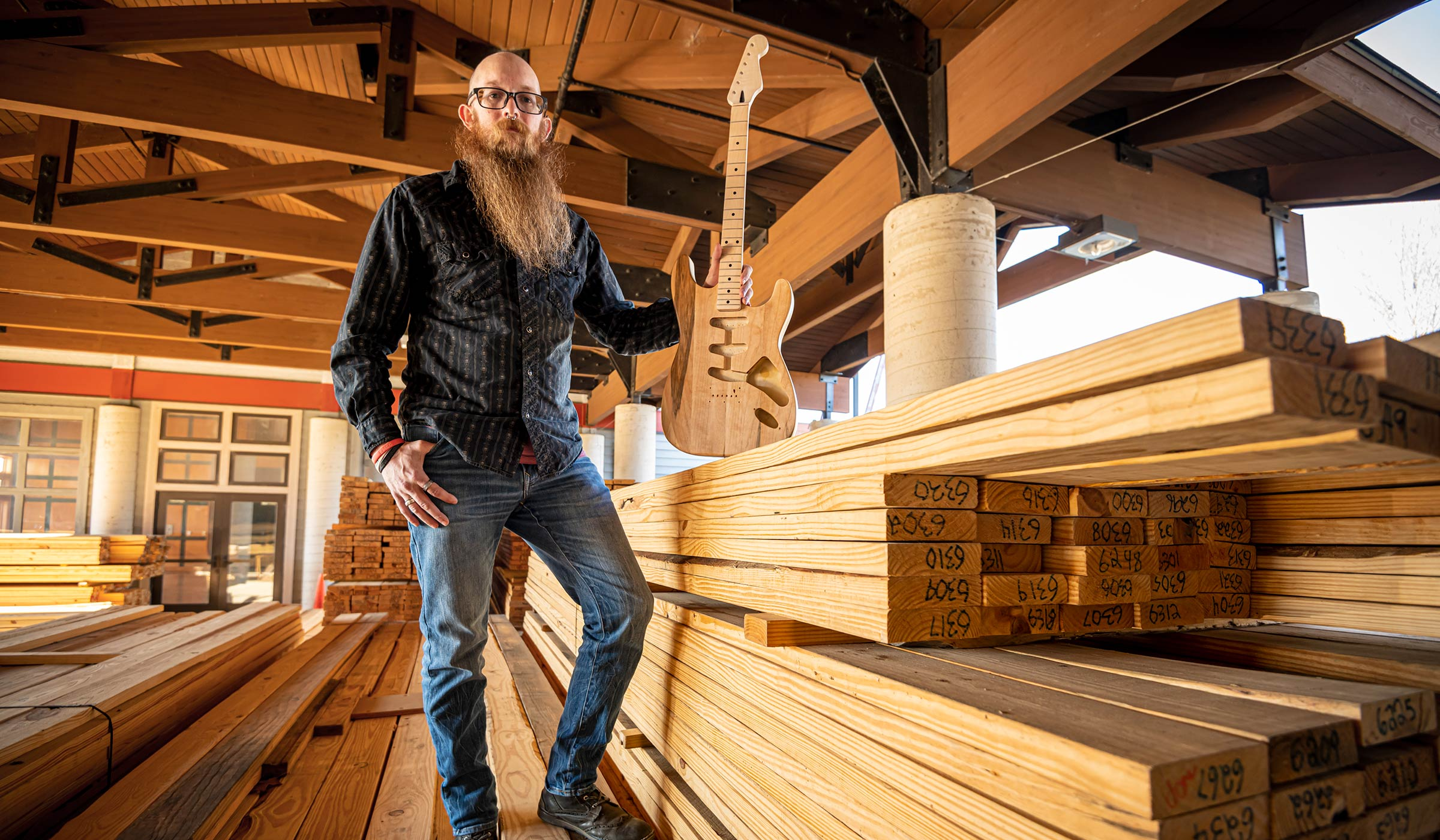 Adam Wade, pictured with a guitar and standing on a pile of lumber.
