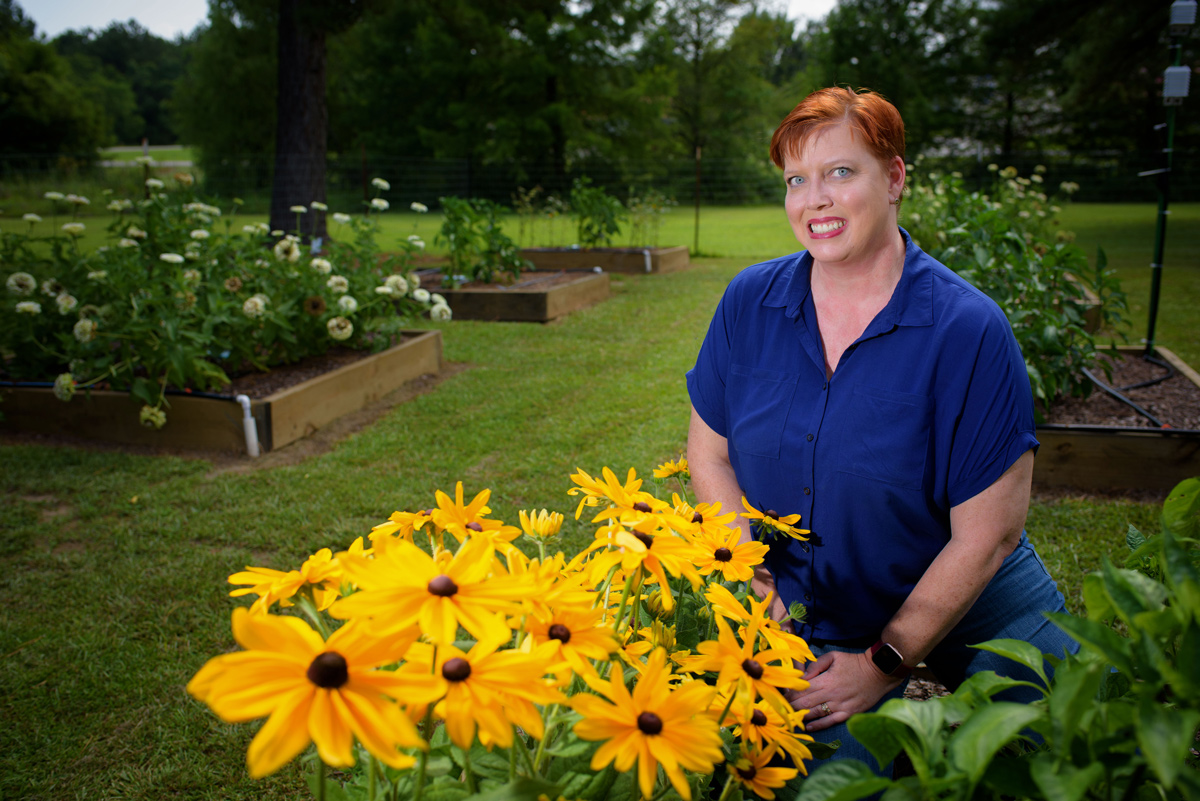 Christine Coker, pictured in a colorful garden.