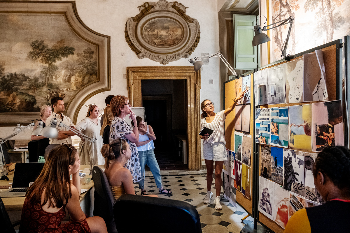 Surrounded by 16th Century decorations on the palace walls of their Rome art studio, CAAD students critique their poster designs