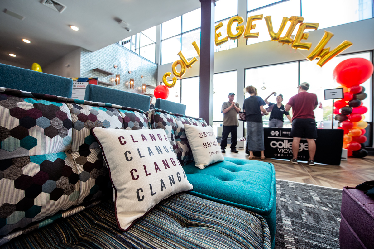 Newly arrived residents check in to College View student housing under balloons and with a Clanga pillow and couch in foreground