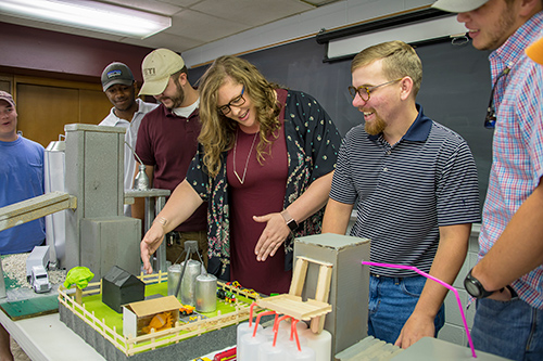 Kelley Wamsley, center, talks with poultry science students about a feed mill model constructed for her course. Pictured from left are Blake Campbell, Caleb Woods, Coleman Lay, Wamsley, Bryce Hollomon and Seth Walters. (Photo by David Ammon)