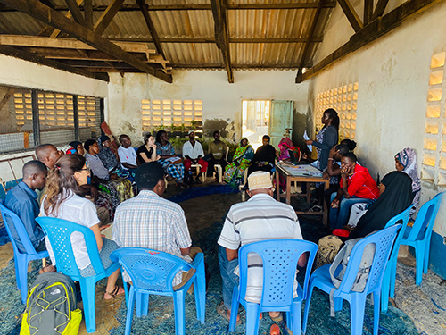 Several people sit and listen to a speaker as Fish Innovation Lab researchers meet with community members in coastal Kenya