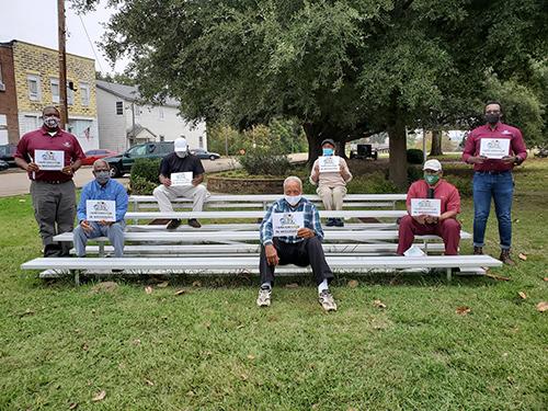 """当他们聚集在当地公园区域时,几个人举着标语""""我在密西西比州正在改变"""""""