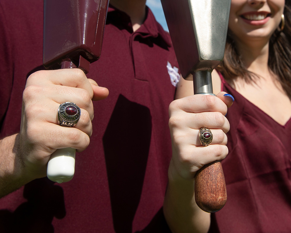 Close up of a man and woman in maroon holding cowbells while showing their MSU class rings