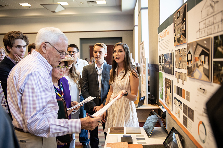 Students look on as Olivia Baker presents her team's Spirit Hill Farm barn renovation project to MSU alumni Bob and Sheryl Bowen.