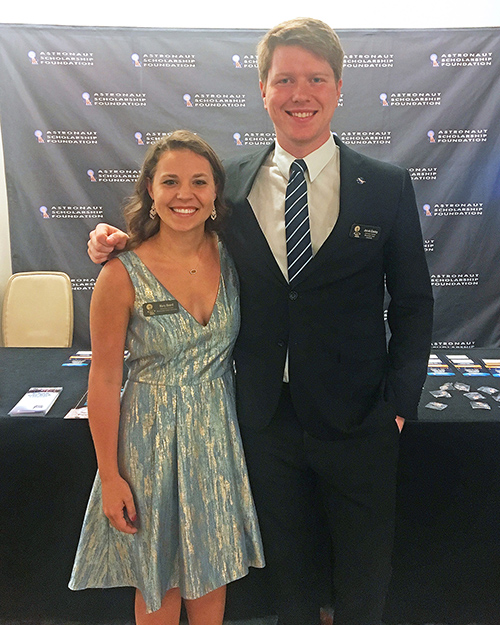 A young lady and man dressed up for a special event smile in front of an Astronaut Scholarship Foundation backdrop