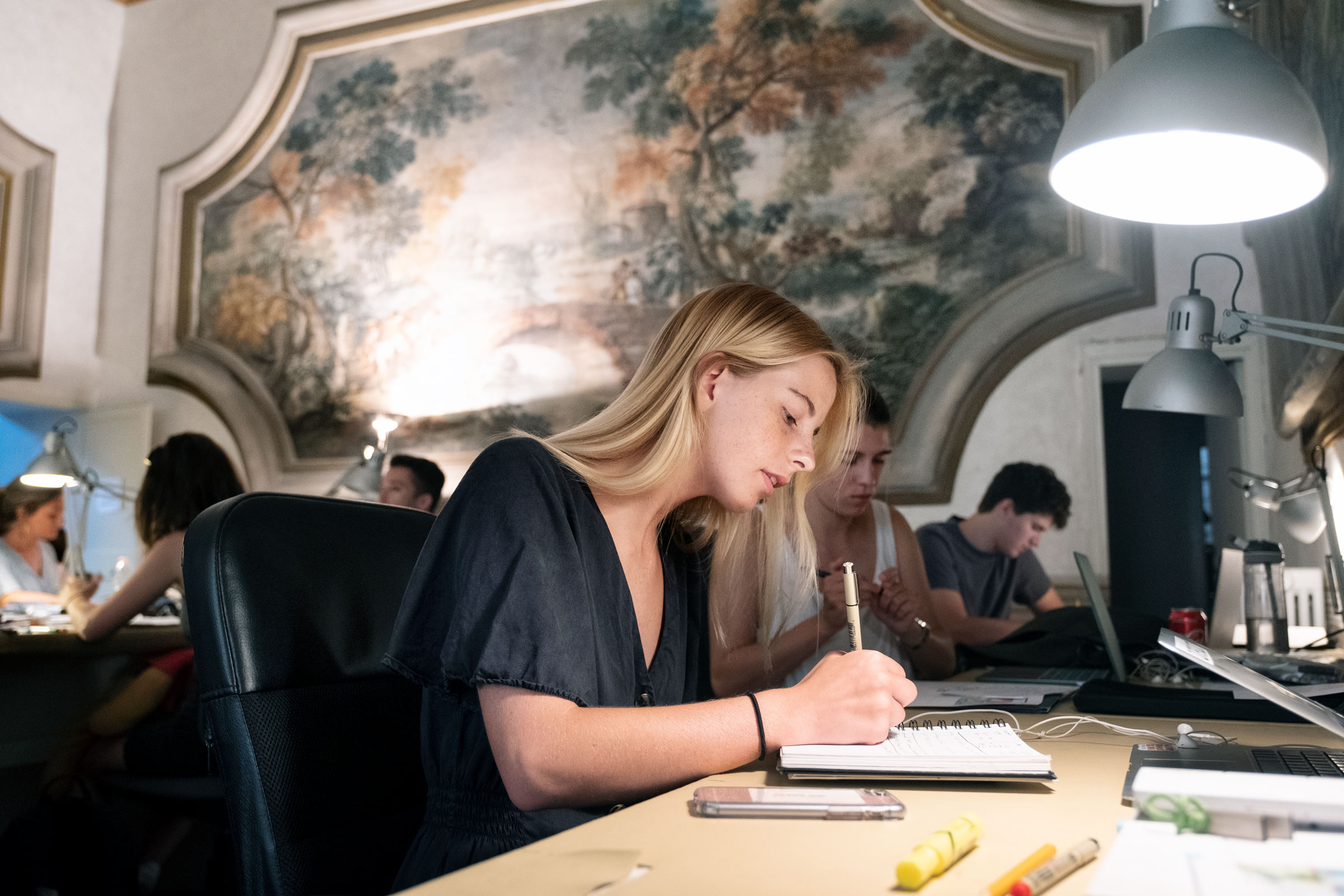 T.J. Barnett writes in a notebook during her study abroad trip in Italy.