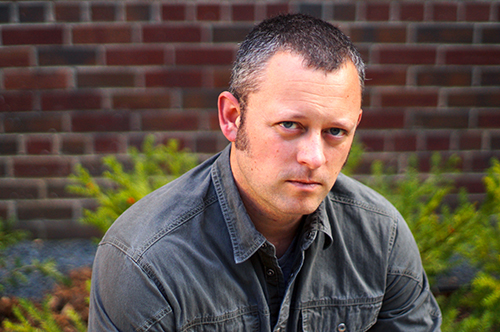 Benjamin Percy stares at the camera while seated in front of a brick wall lined with green plants.