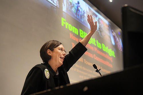 Wendy Benscoter gives a keynote address while standing at a podium in front of a large screen in Harrison Auditorium at Giles Hall.