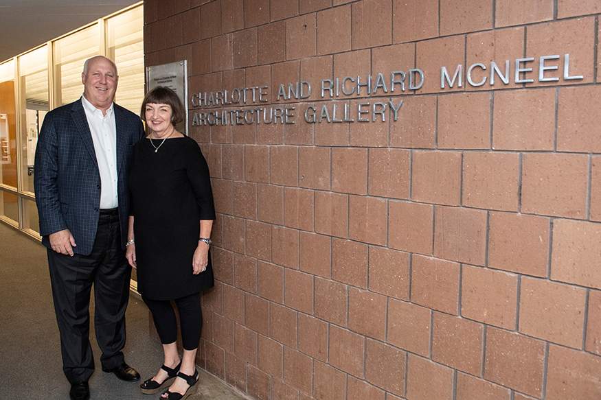 MSU alumni Richard and Charlotte McNeel stand near the sign outside of the Giles Hall architecture gallery that now bears their name.
