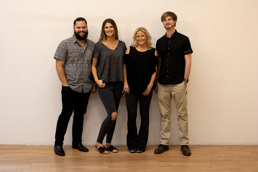 Group photo of four graduating MSU art/graphic design seniors standing in front of a wall
