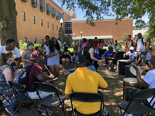 Students participate in a community drum circle near Colvard Student Union