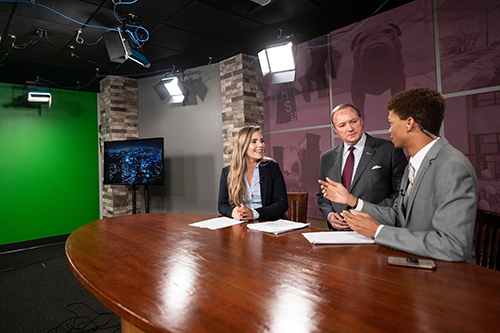 MSU President Mark E. Keenum visits with students using a television broadcast studio, part of MSU's new MaxxSouth Digital Media Center in Mitchell Memorial Library.