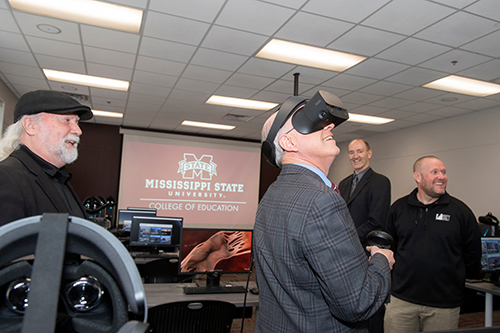 MSU Provost David Shaw smiles and looks around while wearing a virtual reality headset as three other men look on.