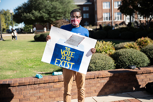 "An MSU student holds a sign reading ""To Vote is to Exist"""