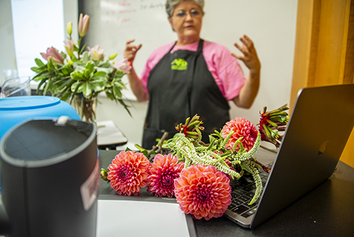 Bright pink flowers are pictured resting on an Apple computer while MSU floral management instructor Lynette Dougald stands in the background.