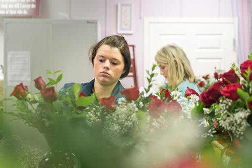 Two female students arrange roses at the University Florist.