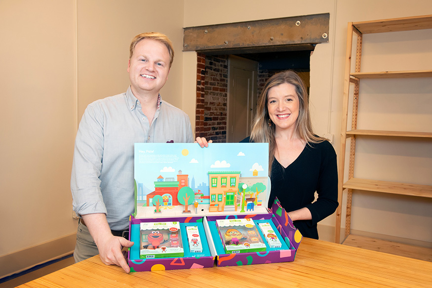 Anna Barker and Hagan Walker hold packages of Glo Pal characters.