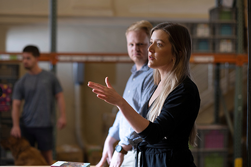 Anna Barker gestures with her hand as she speaks with colleagues in the Glo warehouse.