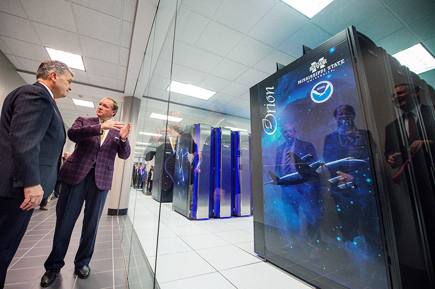 Mark Keenum and Craig McLean talk in front of MSU's Orion Supercomputer