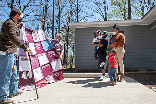 Retired U.S. Army Captain Matt Savage and Starkville resident Dot Livingston present a homemade MSU T-shirt quilt to 12th Maroon Edition homeowners Chadrick Robinson, Santana Turnipseed and two of their children