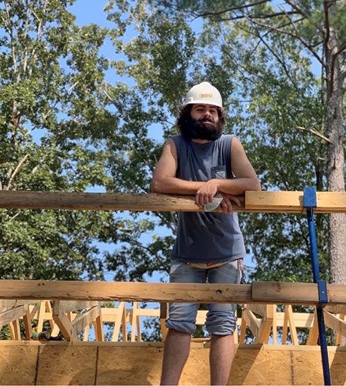戴安全帽的一个年轻人在建设中的房子站立。