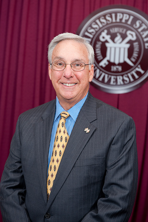 Portrait of Danny Hossley wearing a suit and tie in front of a maroon drape and MSU seal