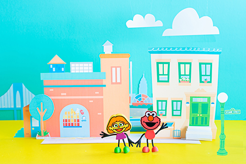 Elmo and Julia characters stand against a Sesame Street backdrop.