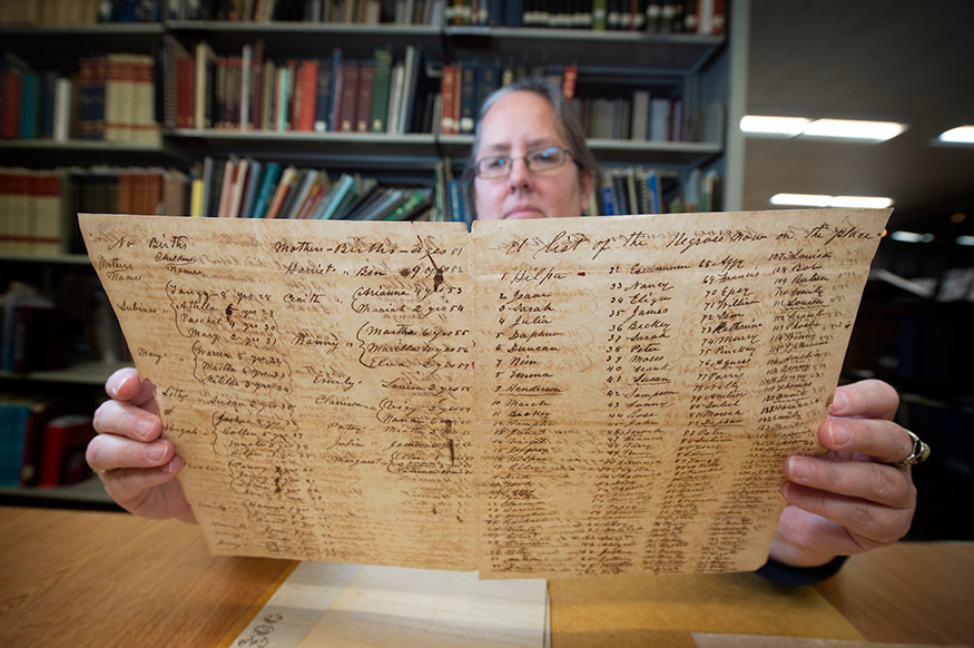 Jennifer McGillan, program director for the Lantern Project, looks over a historical document