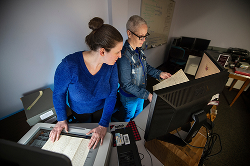 Emily D. Harrison, left, works with Jenifer Ishee to digitize a document for the Lantern Project.