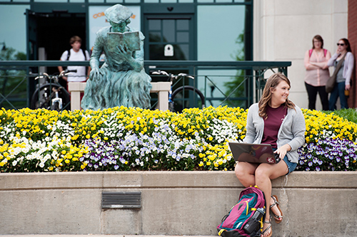 "A student sits outside of Mitchell Memorial Library with her laptop, with flowers blooming and the ""Scholar"" statue in the background"